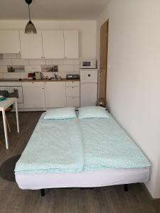 A bed or beds in a room at Green Garden Plus Apartman
