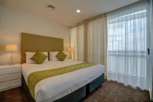 A bed or beds in a room at The Quadrant Hotel & Suites