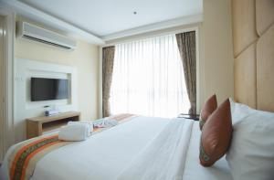 A bed or beds in a room at GM Serviced Apartment