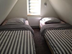 Een bed of bedden in een kamer bij Witte huisje aan zee