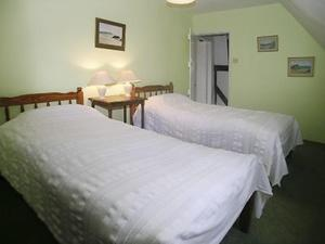 A bed or beds in a room at Oaklawn Cottage
