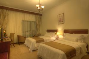 A bed or beds in a room at Siji Hotel Apartments