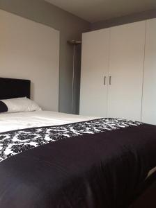 A bed or beds in a room at Bellway Commonwealth Apartment