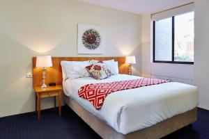 A bed or beds in a room at Manuka Park Serviced Apartments