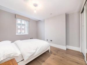 A bed or beds in a room at Valet Apartments Whitehall