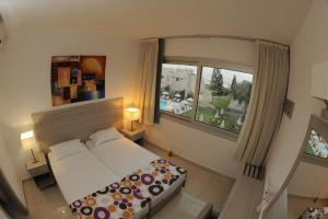 A bed or beds in a room at Frixos Suites Hotel Apartments