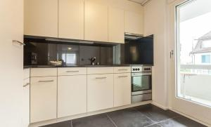 A kitchen or kitchenette at EMA House Serviced Apartments Aussersihl