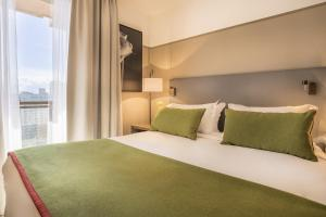 A bed or beds in a room at Fraser Suites Harmonie Paris La Défense