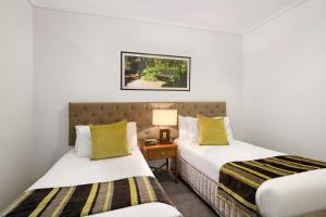 A bed or beds in a room at Quest Jolimont