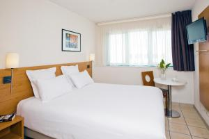A bed or beds in a room at Séjours & Affaires Serris Rive Gauche