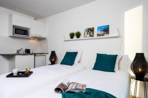 Un ou plusieurs lits dans un hébergement de l'établissement Ténéo Apparthotel Bordeaux Maritime