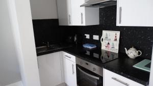 A kitchen or kitchenette at Portum -John St Apartment