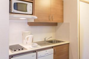 A kitchen or kitchenette at City Résidence Aix-en-Provence