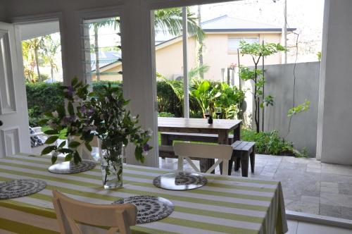 A restaurant or other place to eat at MODERN 3 BEDROOM APARTMENT IN TRADITIONAL QUEENSLANDER , PATIO, LEAFY YARD, POOL