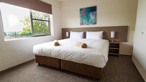 A bed or beds in a room at Adina Place Motel Apartments