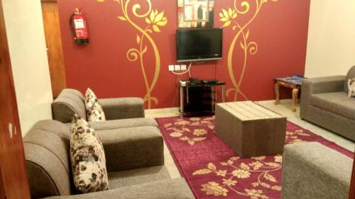 A television and/or entertainment center at Qasr Dalin Furnished Apartments