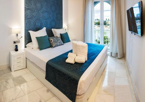 A bed or beds in a room at Betis 7 Luxury Boutique Apartments