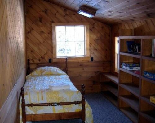 A bed or beds in a room at Kennebago Camp Rental Cabin