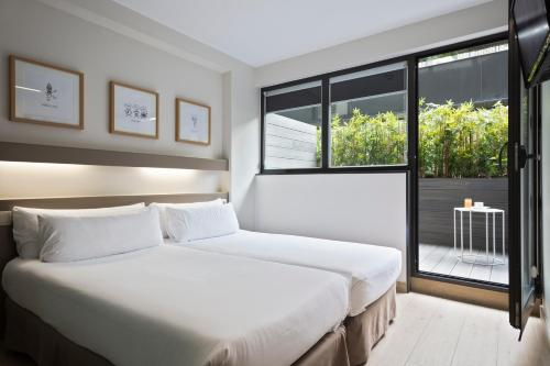 A bed or beds in a room at Aparthotel Bcn Montjuic