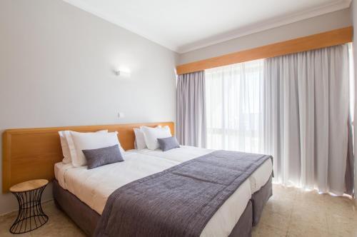 A bed or beds in a room at Clube Praia Mar Apartamentos Turísticos