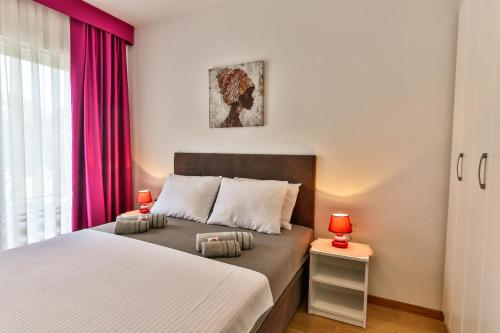 A bed or beds in a room at Apartments Royal Lux