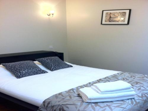 A bed or beds in a room at Lyall Apartment Hotel