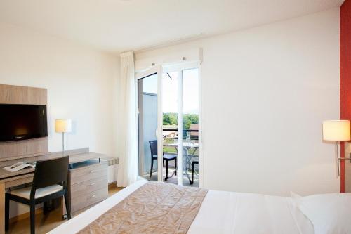 Llit o llits en una habitació de Séjours & Affaires Genève Gex Les Rives Du Léman