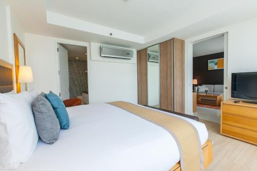 A bed or beds in a room at Oakwood Residence Sukhumvit 24
