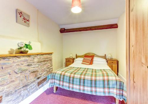 A bed or beds in a room at Yr Hen Ffermdy