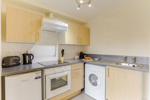 A kitchen or kitchenette at 1BR apartment in a beautiful building, walking distance from the Curve Theatre!