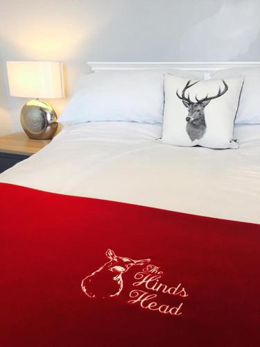 A bed or beds in a room at The Hinds Head Hotel