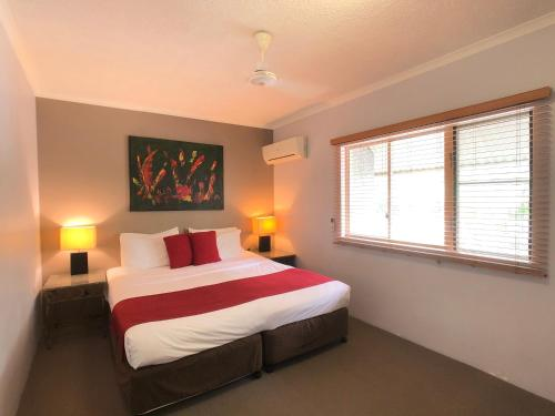 A bed or beds in a room at Cairns Beach Resort