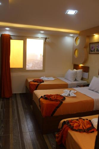 A bed or beds in a room at Osiris Hotel Cairo