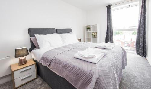 A bed or beds in a room at First Stay Apartments - The West Suite