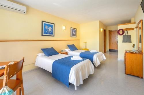 A bed or beds in a room at Apartamentos Tropical Garden