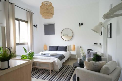 A bed or beds in a room at YARKON - By Beach Apartments TLV