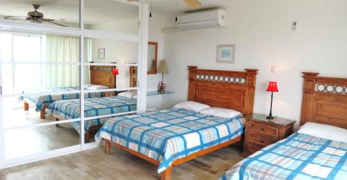 A bed or beds in a room at Cancun Beach Aparthotel Brisas