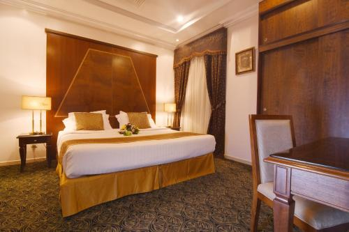 A bed or beds in a room at Al Hamra Palace Hotel & Suites