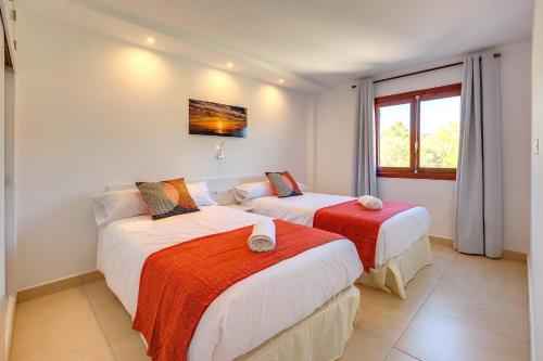 A bed or beds in a room at Camp de Mar Apartments